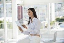 Sonriendo empresaria con tableta digital y sonreír en la oficina - foto de stock