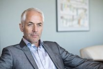 Крупный план уверенного зрелого бизнесмена, сидящего и думающего — стоковое фото