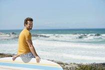 Мужчина сидит на доске для серфинга на пляже и смотрит в камеру — стоковое фото