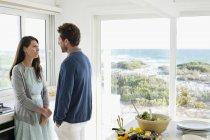Coppia parlando e guardando l'un l'altro in cucina di casa costiera — Foto stock