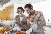 Couple prenant son petit déjeuner au comptoir de la cuisine — Photo de stock