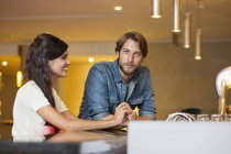 Smiling young couple sitting at a bar counter — Stock Photo