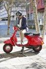 Homme en casque debout avec scooter rouge sur la rue — Photo de stock
