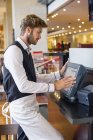 Waiter using computer at checkout counter in a restaurant — Stock Photo