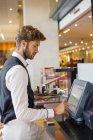 Офіціант, використовуючи комп'ютер в касі боротьби в ресторані — стокове фото