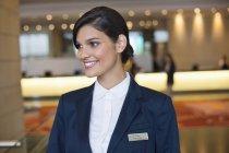 Жіночий портьє, стоячи в фойє готелю і посміхається — стокове фото