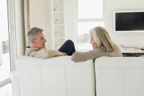 Senior couple sitting on couch in living room and looking at each other — Stock Photo