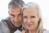 Portrait of romantic senior couple smiling outdoors — Stock Photo