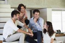Amigos sonrientes sentados en los escalones y hablando - foto de stock
