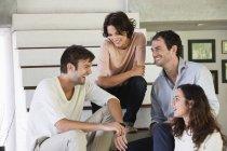 Amici sorridenti seduti sui gradini e che parlano — Foto stock