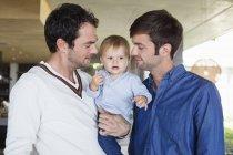 Retrato de feliz lgbt padres sonriendo con hijo en casa - foto de stock