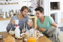 Друзья мужчины сидят за обеденным столом и делятся мобильным телефоном — стоковое фото