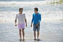 Uomini rilassati che camminano sulla spiaggia con il mare ondulato — Foto stock