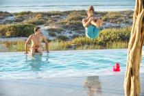 Amigos hombres disfrutando en la piscina en la playa - foto de stock