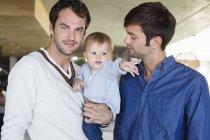 Счастливые родители улыбаются с сыном дома — стоковое фото