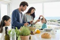 Familia feliz preparando comida en la casa costera - foto de stock