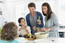 Счастливая семья готовит еду на кухне — стоковое фото