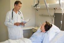 Männlicher Arzt im Gespräch mit Patient auf Krankenhausbett — Stockfoto