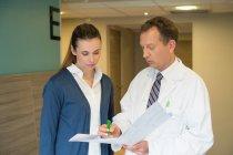 Doutor masculino que discute o relatório médico com a mulher no hospital — Fotografia de Stock