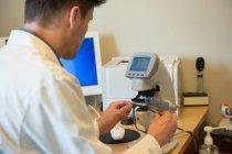 Optometrista masculino examinando equipo de prueba ocular - foto de stock