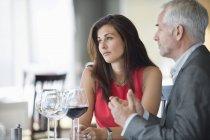Casal desfrutando de vinho tinto no restaurante — Fotografia de Stock