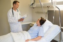 Male doctor talking with patient on hospital bed — Stock Photo