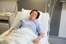 Улыбающаяся взрослая женщина лежит на больничной койке и смотрит в камеру — стоковое фото