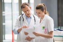 Два врача обсуждают медицинское заключение в больнице — стоковое фото