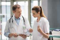 Due medici che analizzano il rapporto medico su tablet digitali in ospedale — Foto stock