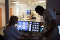 Ärzte untersuchen Scan am Computer mit Patient auf Mri-Scanner im Hintergrund — Stockfoto