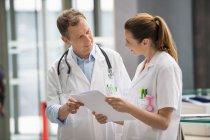 Два доктора аналіз медичного звіту про цифрову таблетку в лікарні — стокове фото