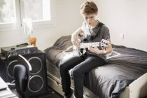 Teenage boy playing guitar at home — Stock Photo