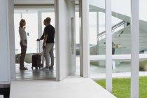 Mujer hablando con amigos con maleta en casa - foto de stock