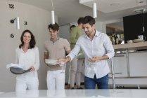 Щасливі друзі носіння страв на обід в домашніх умовах — стокове фото