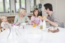 Happy family having fun at breakfast table — Stock Photo