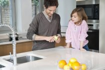 Man preparing breakfast with daughter standing in kitchen — Stock Photo