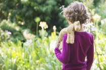 Rear view of little boy standing in meadow with stuffed toy on shoulder — Stock Photo