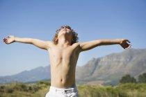 Menino sem camisa de pé com os olhos fechados e braços estendidos contra as montanhas — Fotografia de Stock