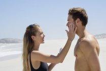 Femme appliquant de la crème solaire sur le visage du mari sur la plage — Photo de stock