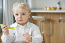 Little boy eating with fork and making face in kitchen — Stock Photo