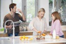 Familia preparando el desayuno en la cocina moderna - foto de stock