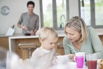 Mother and little son sitting at breakfast table in kitchen with husband on background — Stock Photo