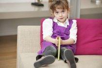 Retrato de una linda niña sosteniendo un libro mientras está sentada en el sofá - foto de stock