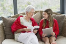Senior woman and granddaughter looking at each other and smiling — Stock Photo