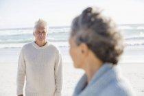 Вдумчивый мужчина смотрит на жену на пляже — стоковое фото