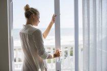 Rilassato giovane donna in piedi alla finestra a casa — Foto stock