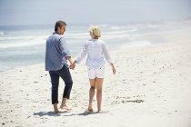 Visão traseira do casal romântico andando na praia de mãos dadas — Fotografia de Stock