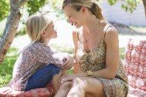 Мать и маленькая девочка сидят на заднем дворе летом — стоковое фото