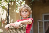 Portrait of little boy holding basket of fresh picked apples outdoors — Stock Photo