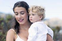 Donna felice che porta bambino all'aperto — Foto stock